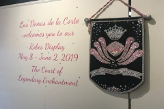 "Las Doñas de la Corte logo with a welcome statement reading ""Las Doñas de la Corte welcomes you to our Robes Display May 8 through June 2, 2019 The Court of Legendary Enchantment"""